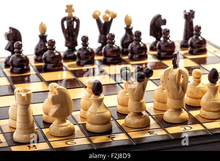Wooden chess pieces lined up on a board ready to play a game or match - Stock Photo
