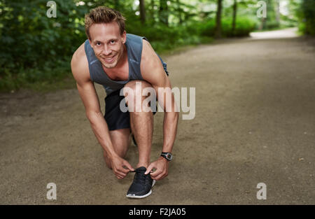 Healthy Muscular Man Smiling at the Camera While Fixing his Shoelace at the Park. - Stock Photo