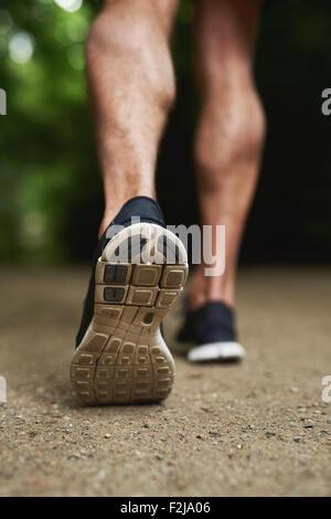 Close up Shoe Sole of an Athletic Young Man Running at the Park - Stock Photo