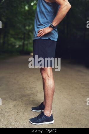 Headless Shot of an Athletic Young Man in Side View, Standing at the Park with Hand on Waist. - Stock Photo