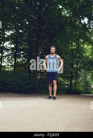Athletic Young Man Standing at the Park with Hands Holding his Waist and Looking Into the Distance. - Stock Photo