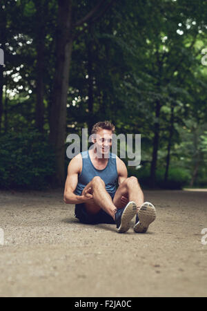 Athletic Young Man Sitting on the Ground at the Park and Flexing his Legs as Warm-up Exercise, with Happy Facial - Stock Photo