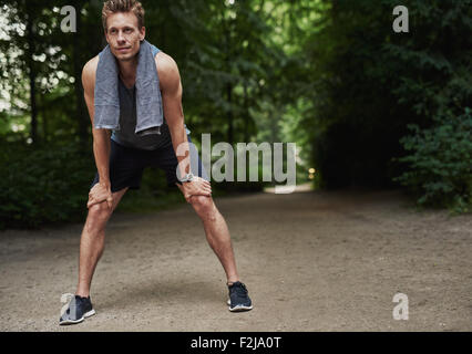 Fit Young Man Holding his Knees While Resting After a Running Exercise at the Park. - Stock Photo