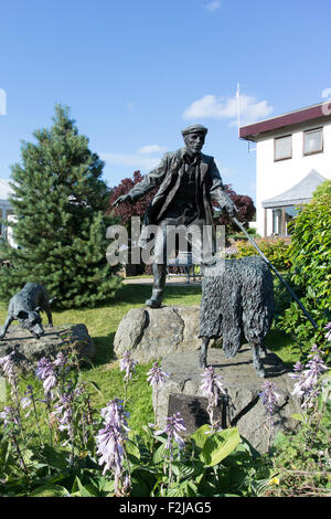 Bronze statue of shepherd and collie sheepdog with a sheep at the Royal Welsh Showground, Wales. - Stock Photo