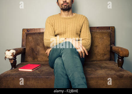 Young man sitting on sofa with book - Stock Photo
