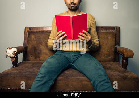 Young man on sofa reading book - Stock Photo