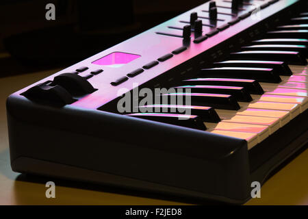 Deatil of a midi keyboard with modulation wheel, lit by a computer screen. - Stock Photo