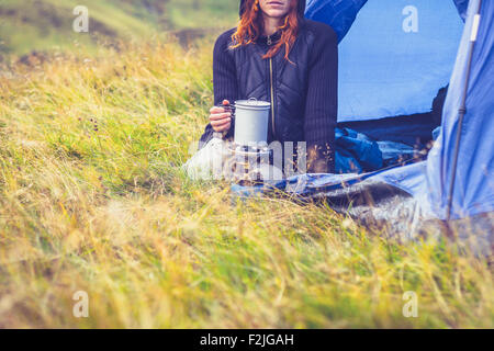 Young woman in tent cooking with portable stove - Stock Photo
