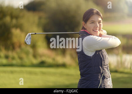 Smiling friendly young woman golfer looking at the camera after following through with her club after the shot, close up view of