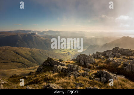 Looking through rising mist from Crinkle Crags down the Langdale valley, early morning in the English Lake District - Stock Photo