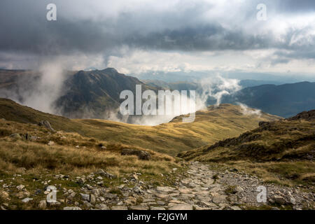 Dramatic clouding rolling up over The Band on Bowfell, looking towards the Langdale Pikes. English Lake District, UK