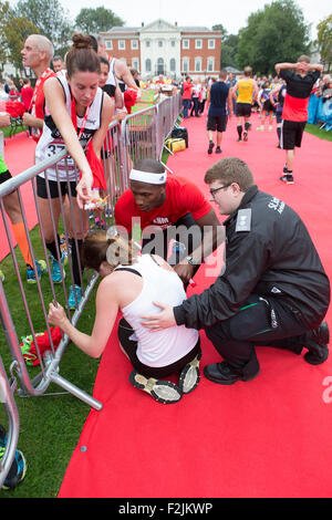 Warrington, UK. 20th September, 2015. A runner is suffering from exhaustion after completing the 2015 English Half - Stock Photo