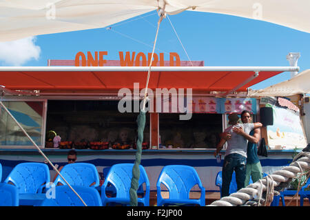 Jaffa, israel: a hug between friends in a bar on the seafront in Old City of Jaffa during a summer day - Stock Photo