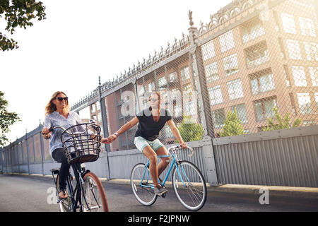 Romantic couple holding hands as they go cycling riding their bikes down an urban street past apartment blocks - Stock Photo