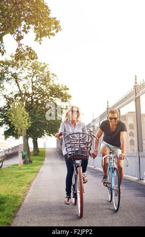 Romantic couple cycling along a cycle path in an urban park holding hands and smiling at the camera on a hot summer - Stock Photo