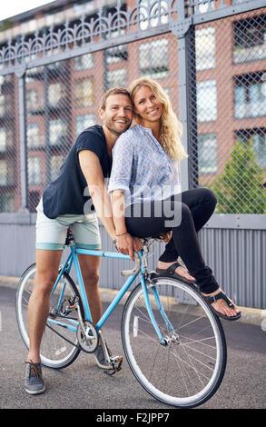Loving couple riding bikes, woman on handlebar - Stock Photo