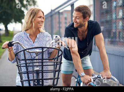 Young couple flirting as they chat in an urban street on their bicycles smiling and looking into each others eyes, - Stock Photo
