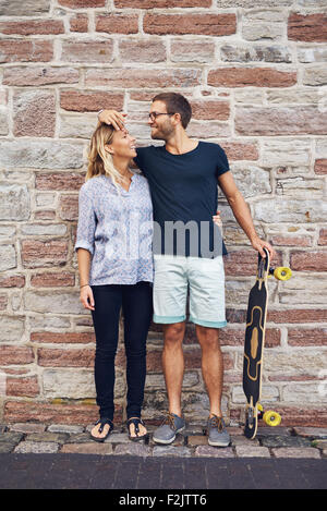 Humorous couple loving each other standing against wall - Stock Photo