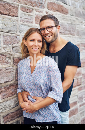 Half Body Shot of a Sweet Man Hugging his Girlfriend From her Behind While Leaning Against Concrete Wall and Smiles - Stock Photo