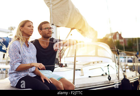 Sweet Young Lovers Sitting In Front of a Yacht and Looking Into the Distance During Sunset. - Stock Photo