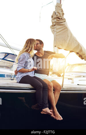 Sweet Young Couple Kissing at the Yacht Deck During Sunset Time. - Stock Photo
