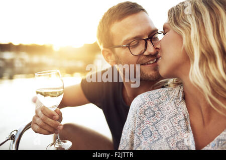 Couple Kissing Gently while Enjoying a glass of Wine - Stock Photo