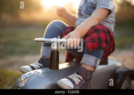 Little racer and tiny race car - Stock Photo