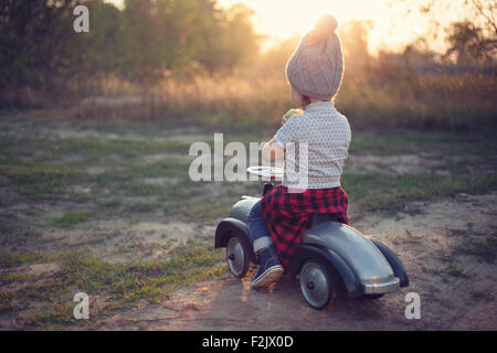Little driver and tiny race car - Stock Photo