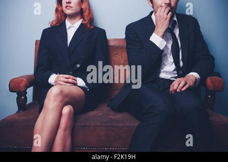 Confident businesswoman and nervous businessman sitting on sofa - Stock Photo