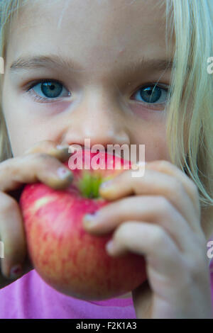 Child blond Girl eating apple, close up - Stock Photo