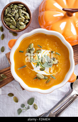 Pumpkin soup with sour cream, herbs and seeds