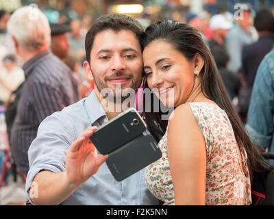 A couple takes a selfie with a smartphone while visiting Times Square in New York City. - Stock Photo