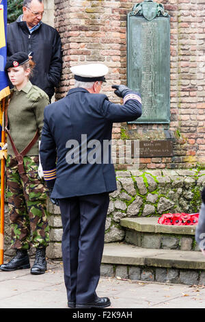 England, Sandwich. Remembrance Sunday. Senior Navy Officer saluting war memorial after laying wreath of poppies, - Stock Photo