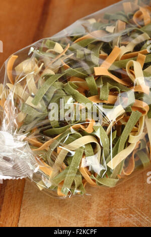 Uncooked Spinach and Tomato Fettuccine in plastic bag - Stock Photo