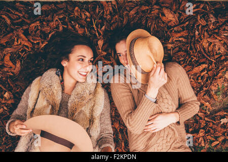 Two smiling female friends lying side by side on autumn leaves in an park - Stock Photo