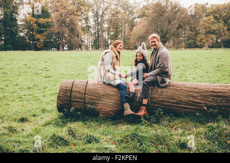 Happy family spending time together in an autumnal park - Stock Photo