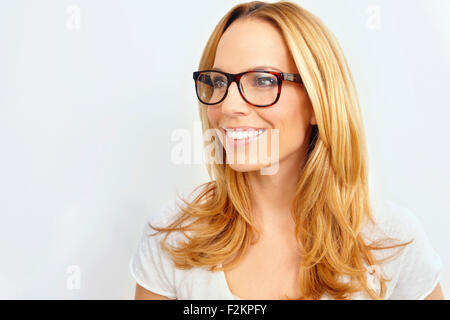 Portrait of smiling blond woman wearing glasses in front of white background - Stock Photo