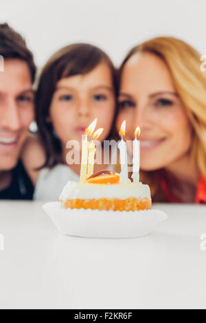 Children's birthday with candles on cake and family in background - Stock Photo