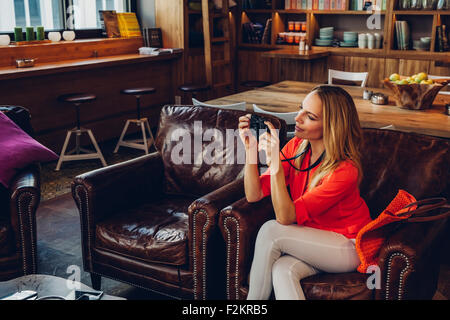 Blond woman sitting in a coffee shop taking pictures with her digital camera - Stock Photo
