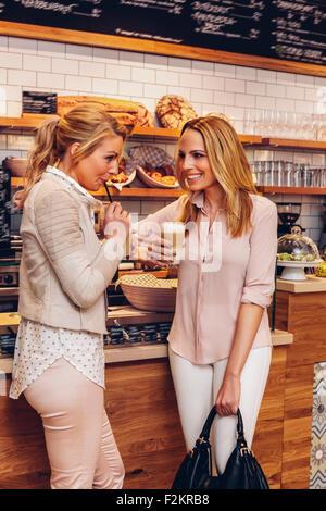 Two female friends drinking Latte Macchiato - Stock Photo