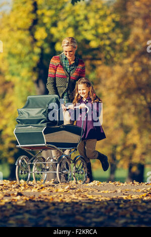 Little girl and her mother pushing a baby carriage in autumnal park - Stock Photo