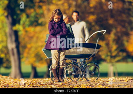 Little girl with crossed arms standing in front of a baby pram in a park with parents in background - Stock Photo