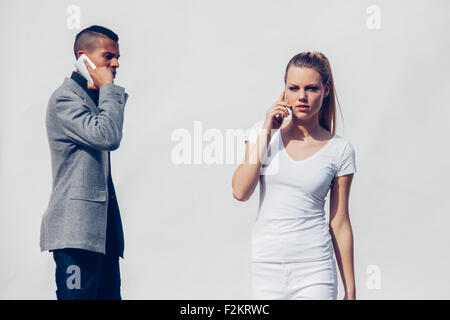 Portrait of white dressed young woman telephoning with smartphone in front of white background - Stock Photo