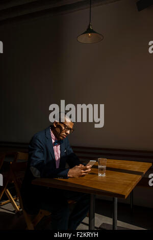 Young man sitting in cafe, waiting for someone, reading text message - Stock Photo