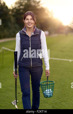 Smiling attractive woman golfer carrying balls in a plastic basket and her clubs on a driving range as she prepares - Stock Photo