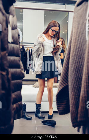 Young woman shopping for shoes in a boutique - Stock Photo