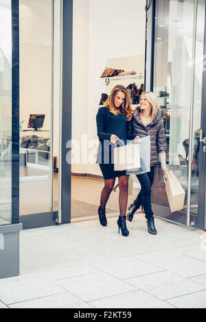 Two happy young women with shopping bags leaving a boutique - Stock Photo
