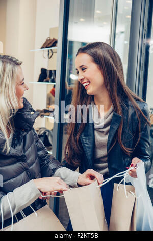 Two happy young women leaving boutique with shopping bags - Stock Photo