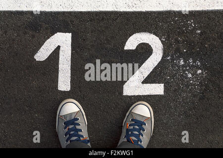 Feet concept with sneakers on asphalt road with 1 and 2 number - Stock Photo
