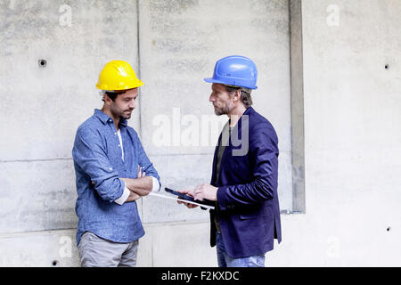 Two men on construction site wearing hard hats - Stock Photo